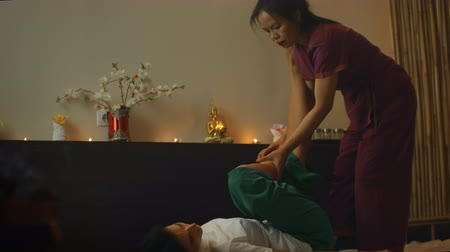 esfregar : Young woman lying down while enjoying the acupressure techniques of traditional Thai massage at luxury spa and wellness center.