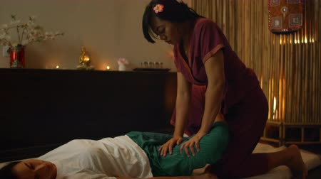 esfregar : Thai massage salon. Asian woman in traditional clothes doing therapeutic relaxing massage, Caucasian woman. Professional traditional massage. Alternative medicine