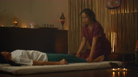 esfregar : Alternative Chinese medicine, an Asian woman performs therapeutic massage movements on the back and legs of a Caucasian woman lying on a couch. Traditional Chinese massage