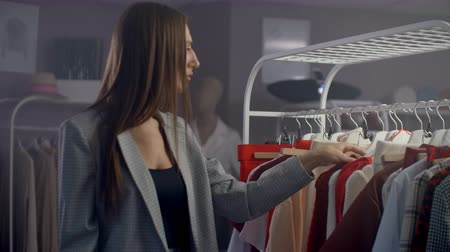 dressing room : Young beautiful girl in a clothing store looking dresses and sweaters on the counter. To take from a hanger and to put to itself smiling
