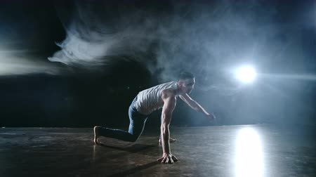 acrobata : Male dancer performs a stunt jump with a rotation back and a revolution in the scene in the smoke in the spotlight. Modern ballet.