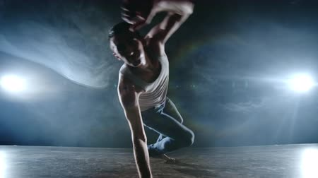 akrobatikus : Modern ballet, a man from a sitting position on the stage jumps somersault with rotation to the camera on a dark stage in the smoke in the spotlight. Modern choreography on the stage of the theater. Stock mozgókép