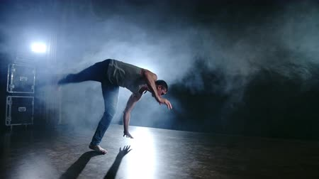 akrobata : Modern ballet, a man from a sitting position on the stage jumps backflip with rotation on a dark stage in the smoke in the spotlight