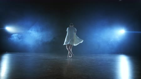 akrobata : Dramatic spins and flips of a modern ballet dancer from a musical. A single woman emotionally dances on stage against a dark background with smoke in the spotlight in slow motion