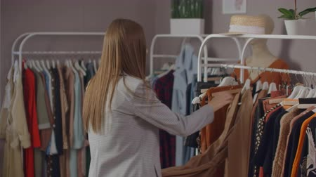 pitka : Young beautiful girl in a clothing store looking dresses and sweaters on the counter. To take from a hanger and to put to itself smiling
