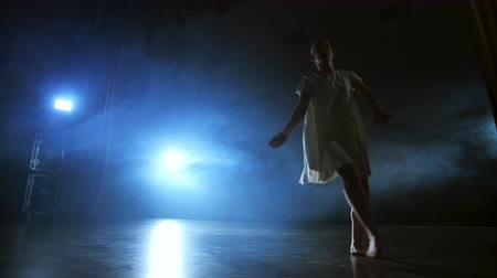 akrobata : A dramatic scene of modern ballet, a lone ballerina in a white dress performs dance steps using modern choreography Stock mozgókép