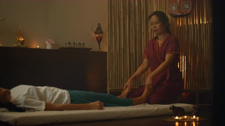 esfregar : An Asian woman performs a traditional Thai massage on the back of a lying beautiful European girl. Chiropractor produces treatment with alternative methods