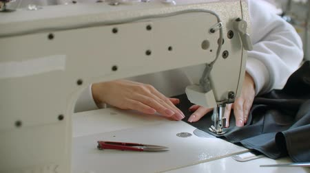 bordado : Seamstress adjusts the sewing machine to work. Young seamstress adjusts the sewing machine to work. Hands close up. Stock Footage