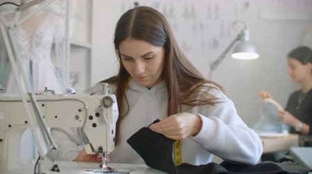 шить : Team work of two tailor and dressmaker who are smile and working on sewing a new collection. The seamstress cuts pattern with scissors and the stylist follows the workflow.