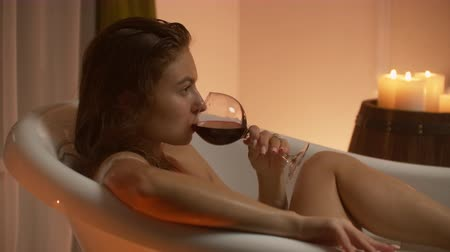banheira : A young beautiful Caucasian brunette lies in the bathroom by candlelight in a pleasant evening atmosphere resting from stress and relaxing drinking red wine from a glass. Stock Footage