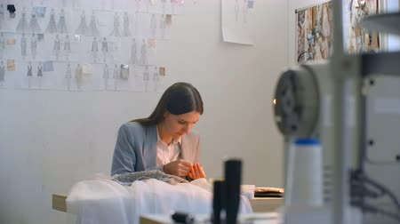 monogramma : A young woman designer making a dress in the Studio dress. Tailoring Studio sewing beads and jewelry. Seamstress decorates a dress in the Studio