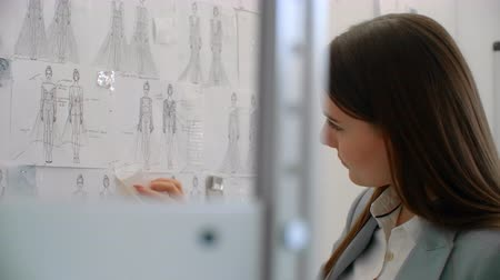 поясница : Young fashion designer standing with back to camera looking at drawings sketches hanging on wall. Woman is thinking about new trendy clothing collection. Стоковые видеозаписи