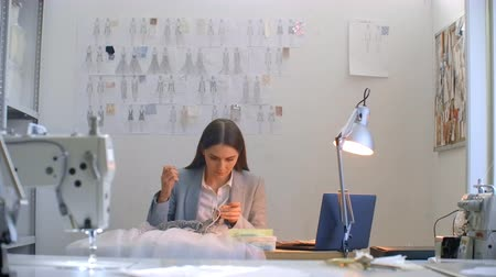 шитье дамского платья : A young girl designer sewing a dress in the Studio dress. Making clothes sewing beads and jewelry. Seamstress decorates a dress in the Studio