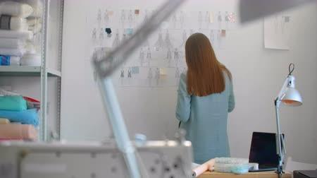 designing : Young fashion designer standing with back to camera looking at drawings sketches hanging on wall. Woman is thinking about new trendy clothing collection Stock Footage