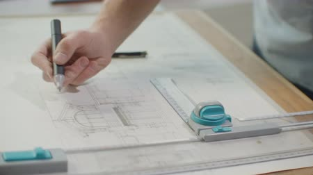 borracha : Engineer draws buildings on the table using a pencil and ruler. An architect creates a building design on paper using a marker and ruler