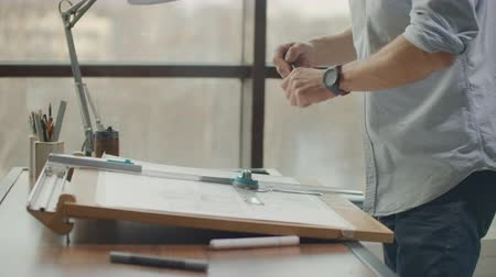 estate agency : architect man Standing working with blueprints sketching a construction project on wood desk at home office.Construction design concept.vintage color tone. Stock Footage