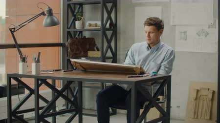 seçkin : Architect man sits at drafting table in modern industrial office during the day Stok Video