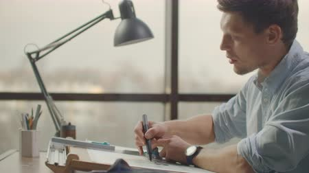 documentatie : Engineer draws buildings on the table using a pencil and ruler. An architect creates a building design on paper using a marker and ruler