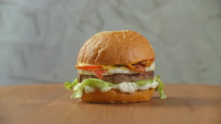 dvojitý : The hamburger spins on a wooden Board. A Burger with a cutlet salad cheese and tomatoes revolves against a gray wall. Dostupné videozáznamy