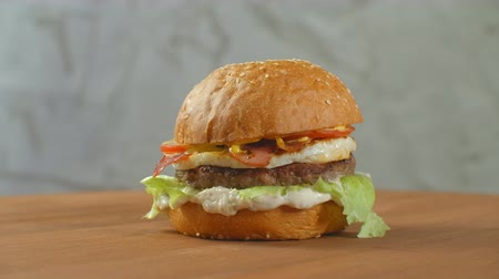 mayonaise : Yummy fast food concept. Fresh homemade grilled burger with meat patty, tomatoes, cucumber, lettuce, onion and sesame seeds. Unhealthy lifestyle. Food background