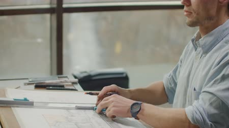 agência : A male architect sitting at a table draws a plan of the building and is engaged in design development, sitting in the office in the Sitel loft near a large window