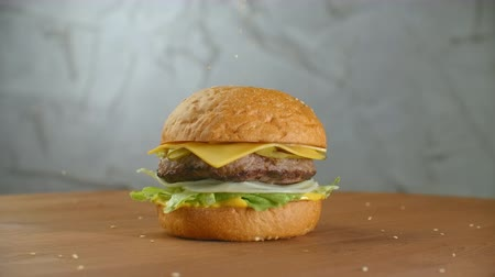 musztarda : In slow motion, sesame seeds fall on a spinning hamburger. Hamburger on a wooden Board.