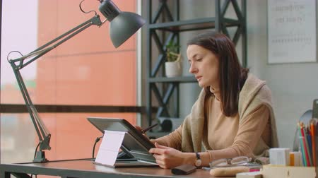 using stylus : A professional designer in the office draws with a stylus on a graphic tablet sitting in an office with huge Windows in the loft style. Modern office of graphic designer and Creator Stock Footage