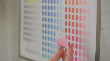 публиковать : Young woman colorist designer picks up colors standing near the wall. Looking at the wall of sketches and flowers. Choose the right color