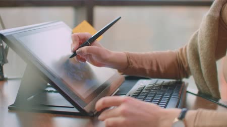 ilustrador : A professional designer in the office draws with a stylus on a graphic tablet sitting in an office with huge Windows in the loft style. Modern office of graphic designer and Creator Archivo de Video