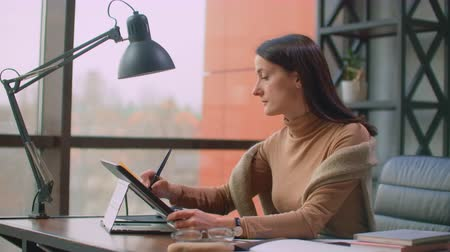 using stylus : A female graphic designer works in an office with large Windows and paints using a stylus and a computer touch screen. Workstation with touchscreen for designers.