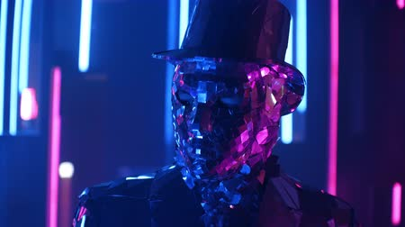 különc : A dancer in a silver suit moves rhythmically in a light reflecting outfit with a hat