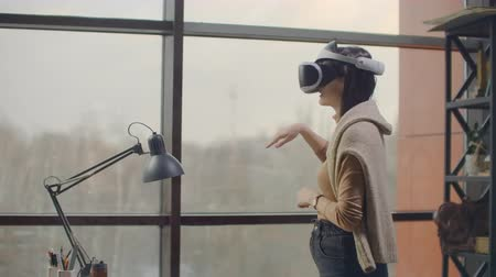 agência : Portrait. Female architect-designer in a virtual reality helmet at in a modern office near a large window with his hands imitates the work of interface. Designing the future