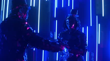 különc : A silver pair of people in love dance together and rotate in neon light. Dancing metal people in costumes