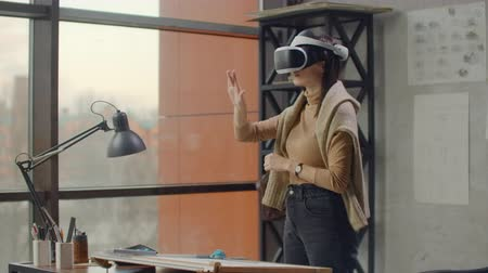 működés : Modern woman engineer-designer in the office with large windows stands in a virtual reality helmet uses gestures to manage the project without leaving the office. Construction control. Design project