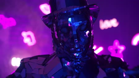különc : Funny diamond man dancing making hand movements in neon blue purple light. Metal suit made of silver
