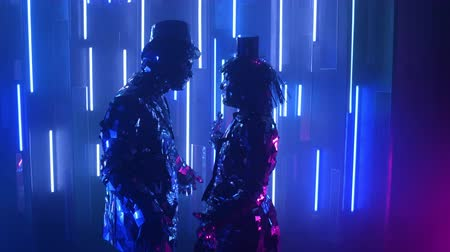 különc : Two robot dancers in glittering costumes dance against a neon wall