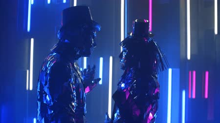 különc : Two dancers a man and a woman standing opposite each other in time to the music dance in glittering mirrored costumes in blue violet the color of shimmering neon