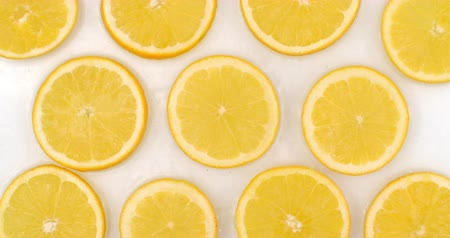 limonada : Top view: on a white background, a many fresh orange is lying in the water, water drops are falling from above and splashes are falling in slow motion in all directions