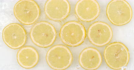 rodajas de naranja : Many fresh lemon, top view of water flowing on a white background Archivo de Video