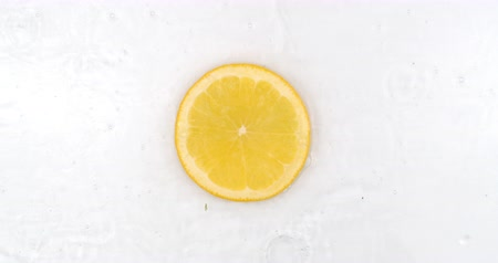 rodajas de naranja : Super Slow Motion Shot of Splashing Water to one orange Slices view from above. Archivo de Video