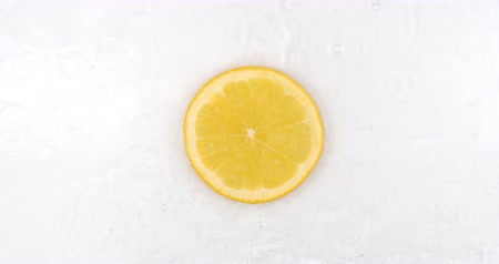rodajas de naranja : Top view: on a white background, a fresh orange is lying in the water, water drops are falling from above and splashes are falling in slow motion in all directions