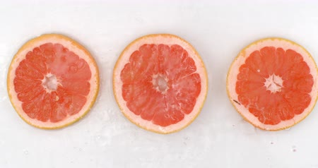 grejpfrut : Super Slow Motion Shot of Splashing Water to grapefruit Slices view from above.