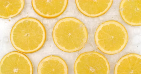 rodajas de naranja : In slow motion, water splashes pour water onto a beautiful juicy citrus fruit many Lemons on a white background.