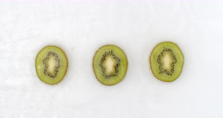 koolhydraten : Slow motion water splash on three slices of green kiwi lying on a white background in the water. Stockvideo