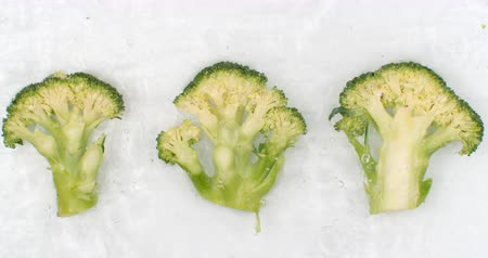 brocoli : Slow motion water splash on three slices of green broccoli lying on a white background in the water.
