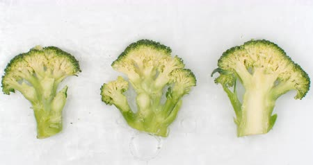 brócolis : In slow motion, splashes of water pour water on a beautiful juicy vegetables a lot of broccoli on a white background. Vegetarian and Fructorians Stock Footage