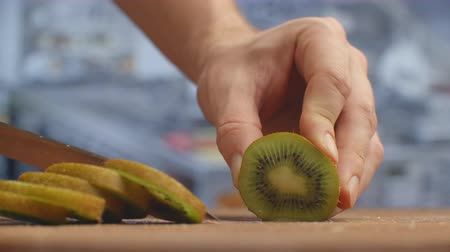 shred : Cut with a knife on a wooden board closeup kiwi in the kitchen. shred. Stock Footage