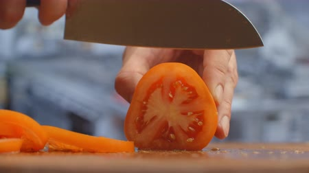 nourishing : Closeup of a woman cutting and chopping tomato by knife on wooden board. Stock Footage