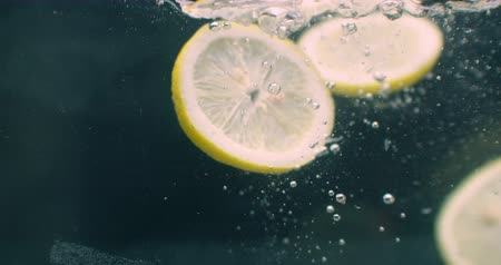 охлажденный : Several lemon fruits fall inside a water tank and disturb water. Three bright yellow lemon fruits fall inside a water tank and return to the surface.