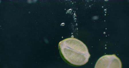 tonik : Lime slices fall and float in water, black background, slow motion. Green lime slices fall and float in water, black background, slow motion. Stok Video